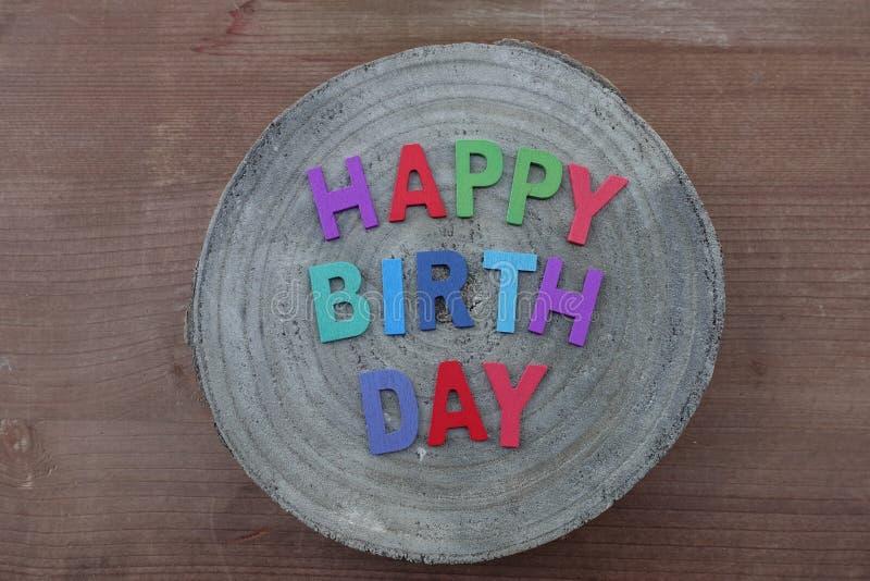 Alles- Gute zum Geburtstagtext mit farbigen hölzernen Buchstaben auf einem hölzernen runden Brett der Mango lizenzfreie stockbilder