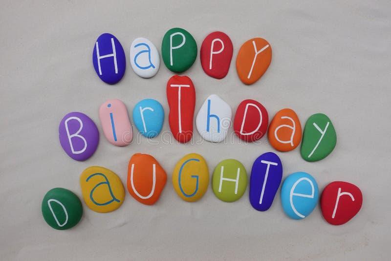 Alles- Gute zum Geburtstagtochter mit farbigen Steinen über weißem Sand lizenzfreie stockfotografie