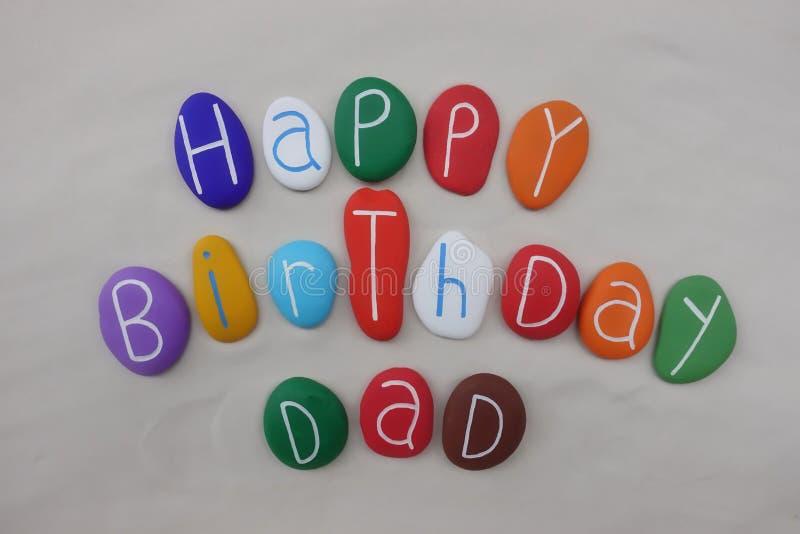 Alles- Gute zum Geburtstagvati mit farbigen Steinen über weißem Sand lizenzfreies stockbild