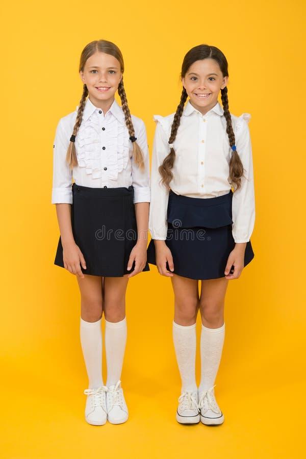 Alles nach rechts machen Ausgezeichnete Schüler Perfekte einheitliche Ausstattung der Mädchen auf gelbem Hintergrund Entsprechend stockbild
