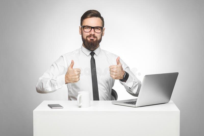 Alles in orde! Het portret van knappe tevreden gebaarde jonge zakenman in wit overhemd en de avondkleding zitten in bureau stock foto's