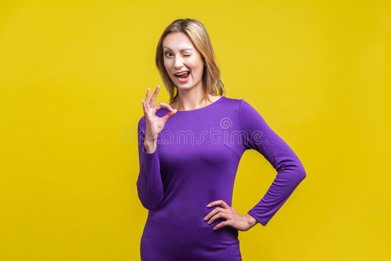 Alles is in orde Portret van een positieve vrouw die een goed gebaar laat zien binnenstudio-opname geïsoleerd op gele achtergrond royalty-vrije stock afbeelding