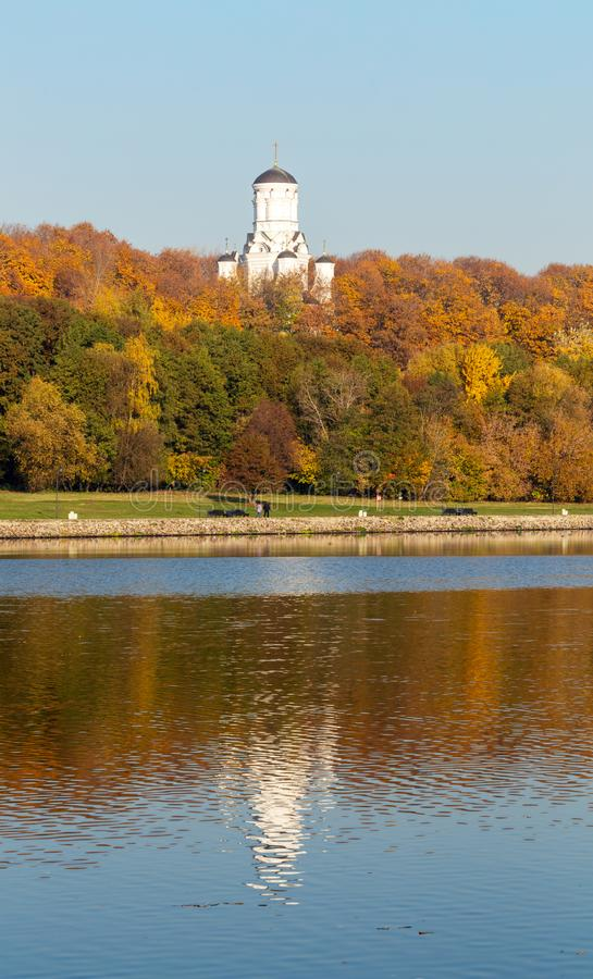 Alley along the riverbank on the background of the autumn park. Tower of the Orthodox Church. Reflections in the water royalty free stock images
