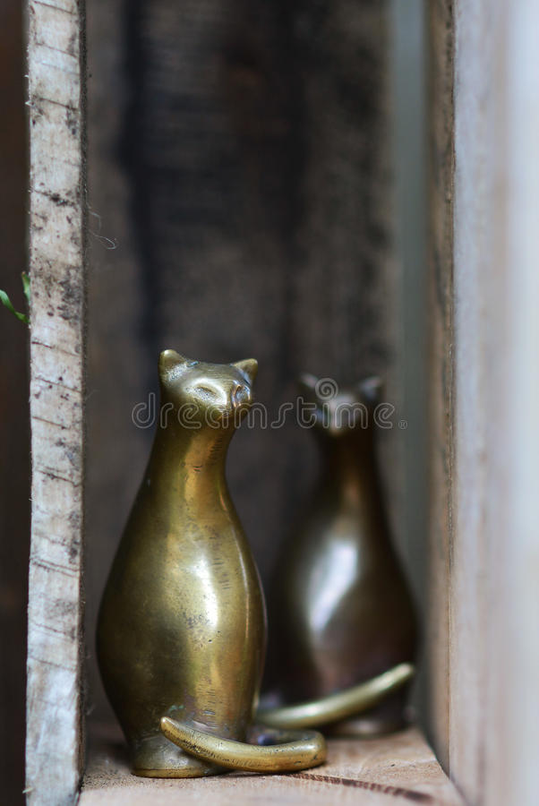Alley cats. Pair of vintage brass siamese cats in rustic weathered pallet stock photos