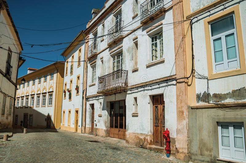 Alley of old colorful terraced houses with worn plaster wall stock photo