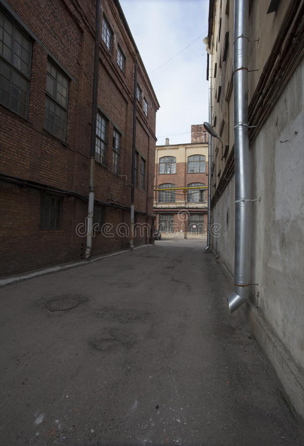 The alley between the old factory buildings inside the factory closed block in an industrial area of old European cities. Lane (travel) between the old factory royalty free stock photo