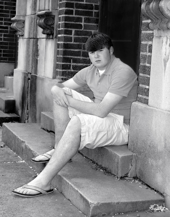 Alley Pose. Teenager poses on alley steps at back of historic building. He is wearing flip flops and shorts and has a serious expression royalty free stock photos