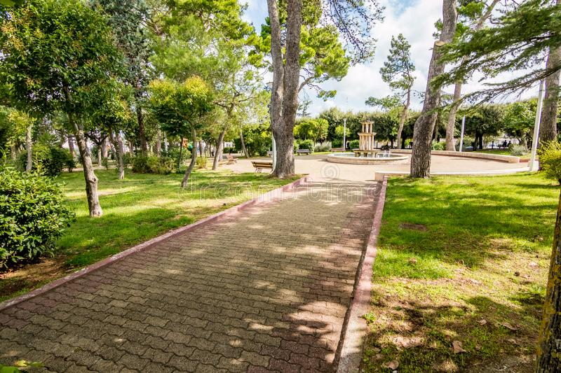 Alley in public park, Noci. Puglia. Italy. Alley in the tree shadows with round square and fountain in public park, Noci. Puglia. Italy, sunny and warm summer stock photos