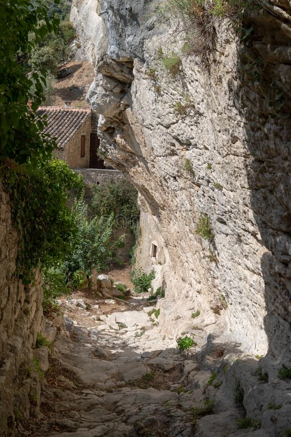 Alley street cut into the rock of the mountain with houses in hilltop village Oppede Le Vieux in Provence France royalty free stock image