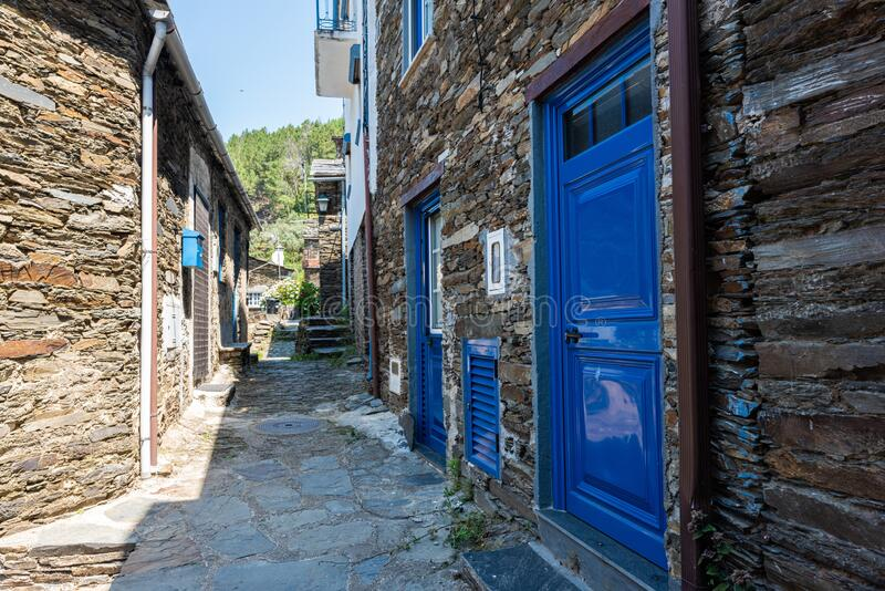 Alley surrounded by buildings with colorful doors under sunlight in Piodao village in Portugal stock image
