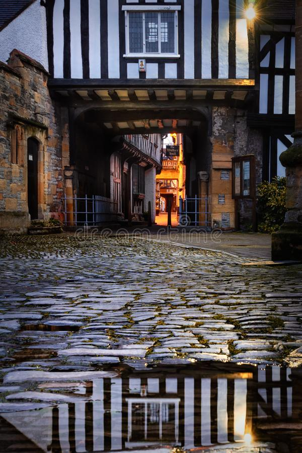 Evesham in worcestershire. Alleyway through black and white timber framed building with reflection on cobblestone road royalty free stock photography