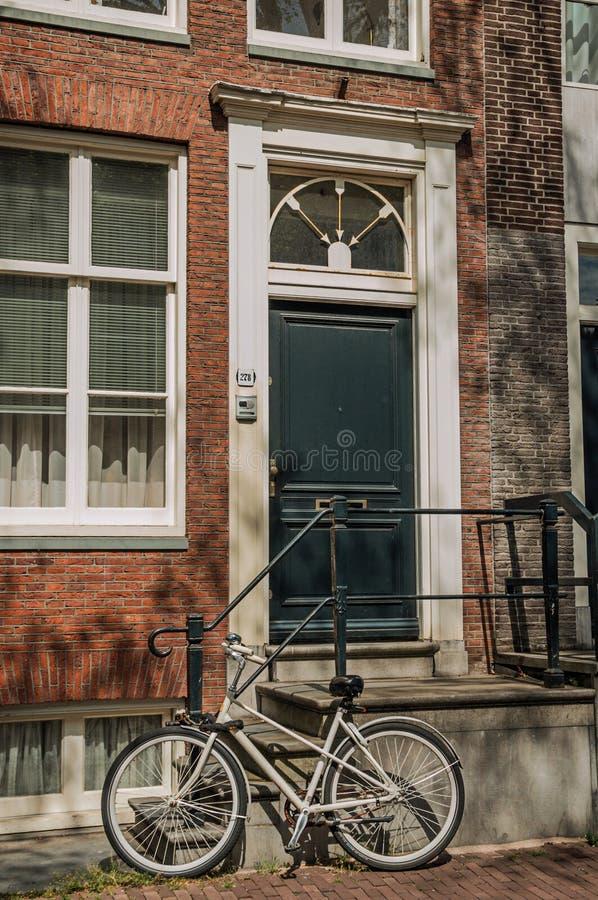 Allez à vélo devant des escaliers à l'entrée du vieil immeuble de brique élégant à Amsterdam photo libre de droits