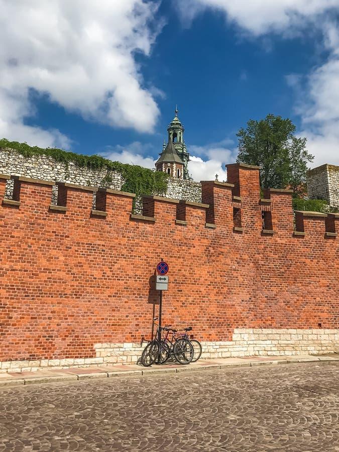 Allez à vélo le stationnement sous le mur du château royal de Wawel à Cracovie, Pologne photo libre de droits