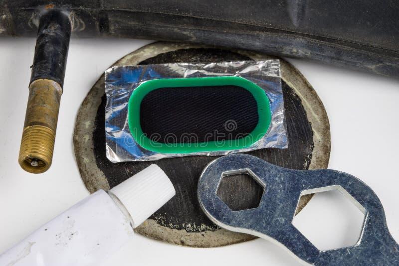 Allez à vélo le tube, la colle et les corrections dans l'atelier Réparation d'un dama photo stock