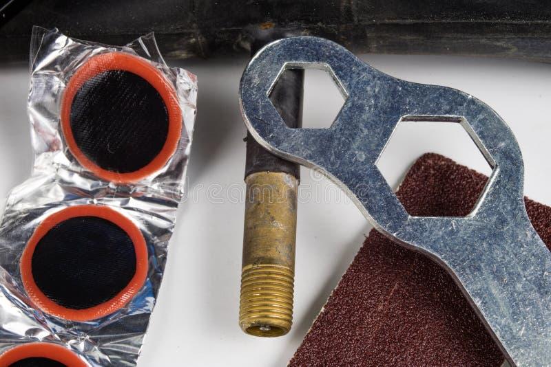 Allez à vélo le tube, la colle et les corrections dans l'atelier Réparation d'un dama photographie stock libre de droits