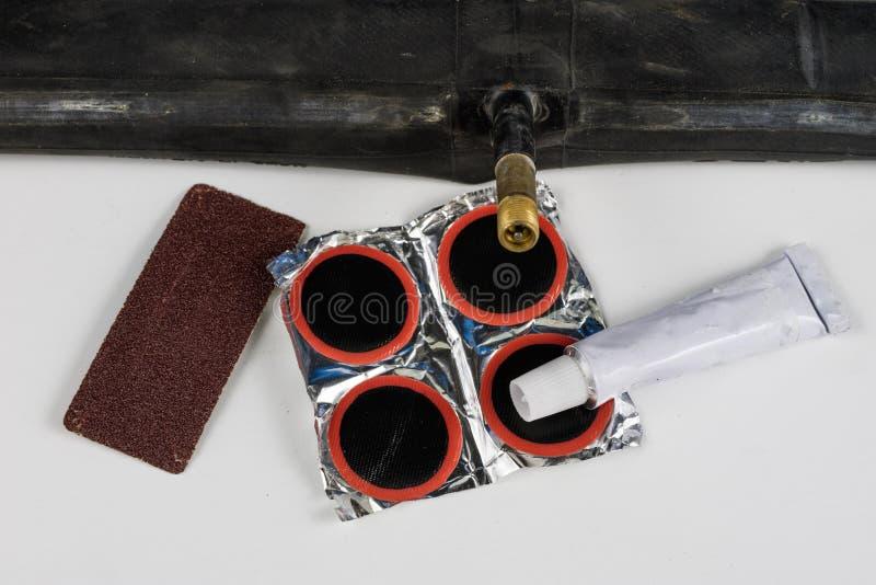 Allez à vélo le tube, la colle et les corrections dans l'atelier Réparation d'un dama images stock