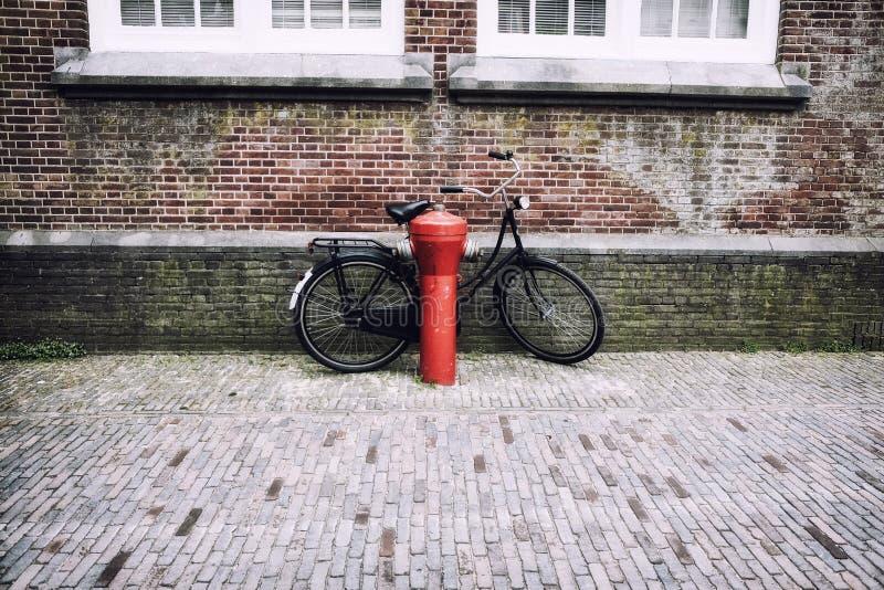 Allez à vélo près de la bouche d'incendie rouge en Hollande images libres de droits