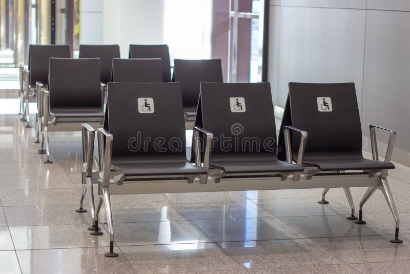 Allgemeine Sitze der leeren Priorität für Behinderter Weißes Zeichen mit einem Handikapmann in einem Rollstuhl lizenzfreie stockfotografie