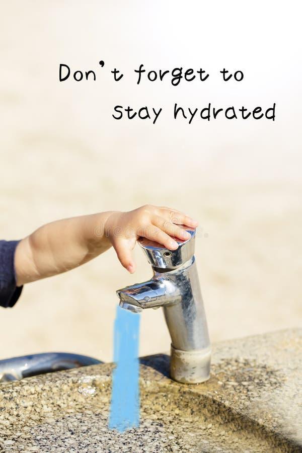 Allgemeiner Trinkbrunnen mit child's kleiner Hand im Stadtpark Don't vergessen, hydratisiert zu bleiben stockbild