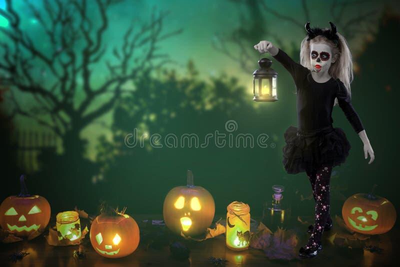 Allhelgonaafton ferier, maskeradbegrepp - ståenden av den unga lilla härliga flickan med skallemakeup på pumpabakgrund Mummel royaltyfria foton
