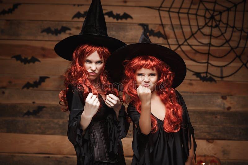 Allhelgonaaftonbegrepp - härlig caucasian moder och hennes dotter med långt rött hår i den gladlynta häxadräkthäxan royaltyfri foto