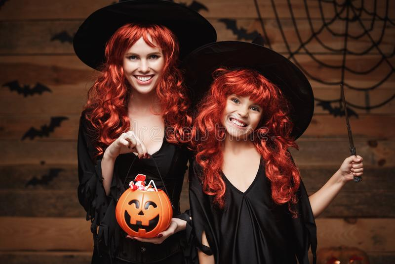 Allhelgonaaftonbegrepp - härlig caucasian moder och hennes dotter med långt rött hår i häxadräkter med allhelgonaafton royaltyfria foton