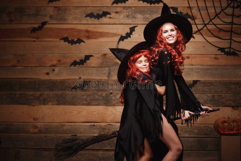 Allhelgonaaftonbegrepp - härlig caucasian moder och hennes dotter med långt rött hår i häxadräkter som flyger med magi royaltyfria foton