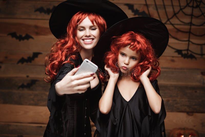 Allhelgonaaftonbegrepp - härlig caucasian moder och hennes dotter med långt rött hår i häxadräkter som tar en selfie royaltyfri fotografi