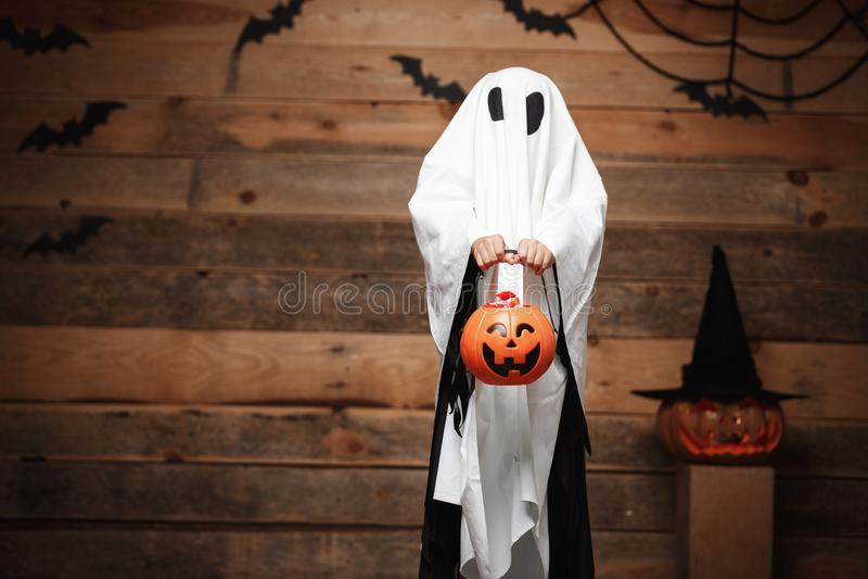 Allhelgonaaftonbegrepp - liten vit spöke med kruset för halloween pumpagodis som gör trick eller fest med krökta pumpor över royaltyfri foto