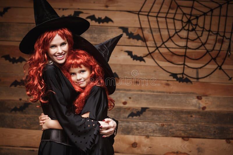 Allhelgonaaftonbegreppet - härlig caucasian moder och hennes dotter med långt rött hår i lyckligt le för häxadräkter och kramar v royaltyfri bild