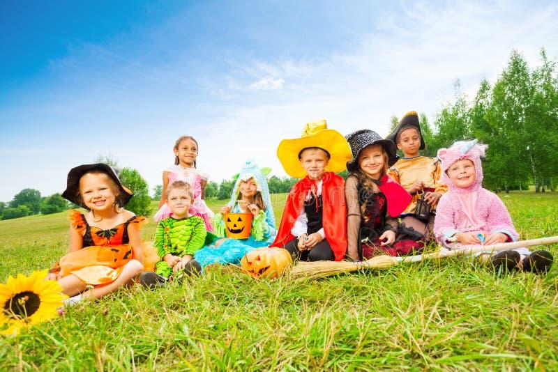 Allhelgonaaftonen med ungar i dräkter sitter utanför royaltyfri foto