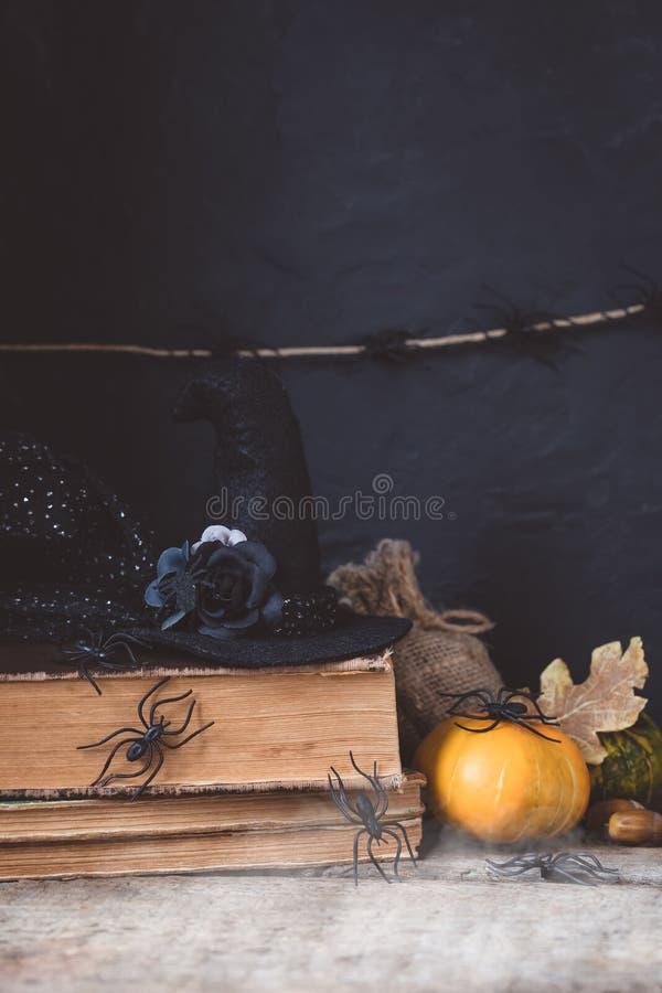 Allhelgonaaftonferiebakgrund med pumpa, lykta, spindlar, gamla böcker, svart witchhat arkivfoton