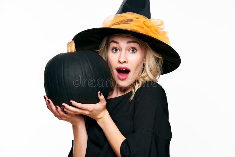 Allhelgonaaftonhäxa med det chockade uttryckt som rymmer stor svart pumpa Härlig ung kvinna i hållande pumpa för häxahatt arkivfoto