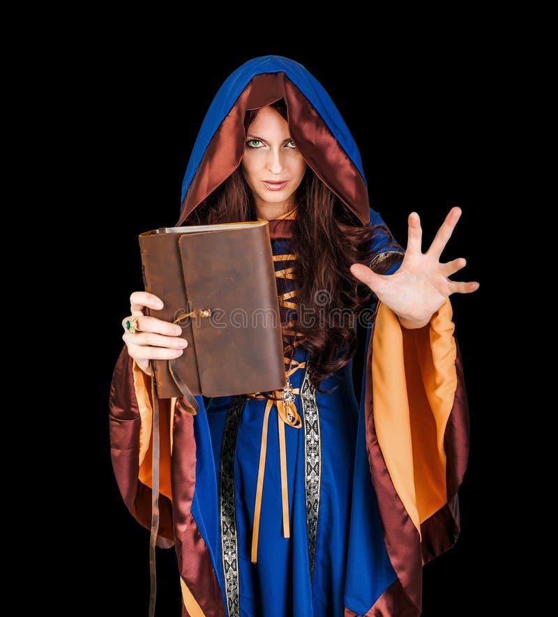 Allhelgonaaftonhäxa som rymmer den magiska boken av pass som gör magi royaltyfri foto