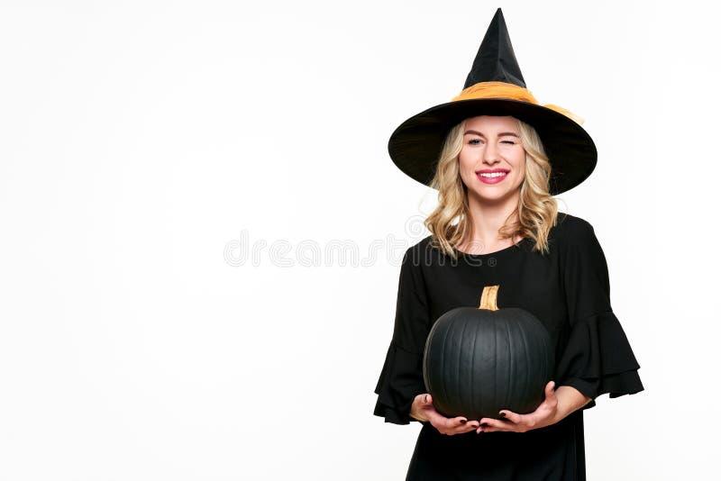 Allhelgonaaftonhäxa som rymmer stort svart blinka för pumpa Härlig ung kvinna i häxor hatt och hållande pumpa för dräkt arkivfoton