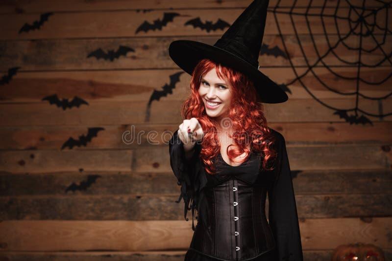 Allhelgonaaftonhäxabegrepp - för hårhäxa för lycklig allhelgonaafton som rött innehav poserar med trollspöet över gammal trästudi royaltyfri foto
