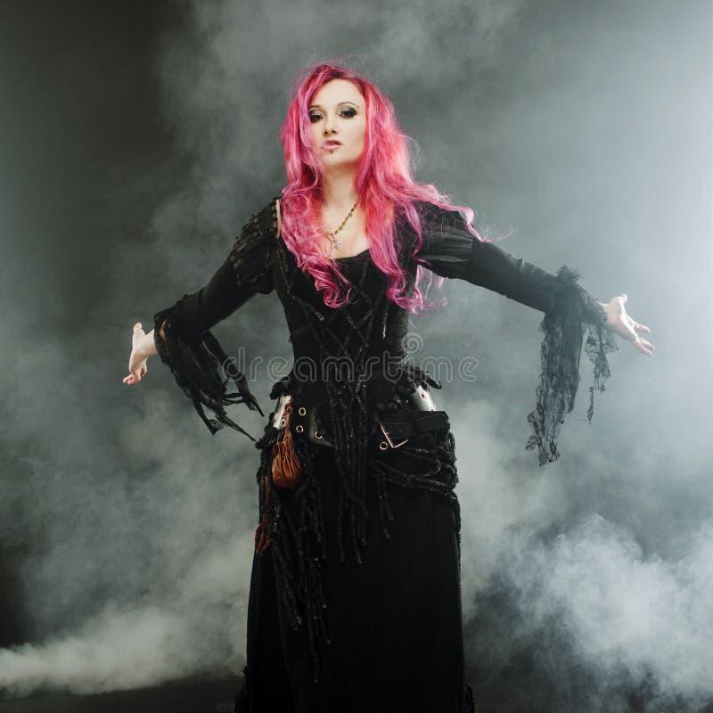 Allhelgonaaftonhäxan skapar magi Den attraktiva kvinnan med rött hår i häxor kostymerar stående utsträckta armar, stark vind royaltyfri bild