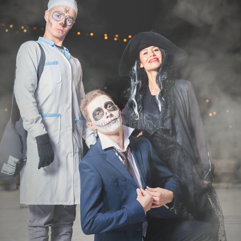 Allhelgonaaftonmaskeradkläder av häxan, doktorn och stålar - ledar- pumpa arkivfoton
