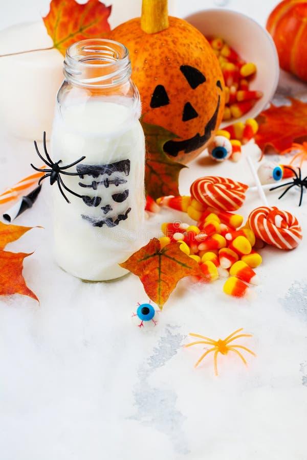 Allhelgonaaftonpartiuppsättning - drinkar, godisar och dekor på vit bakgrund royaltyfri foto