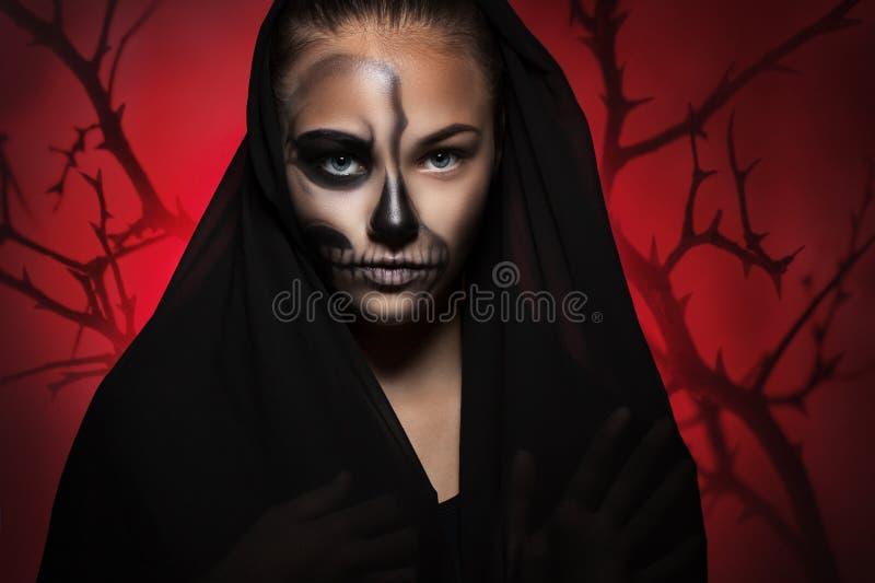 Allhelgonaaftonstående av den unga härliga flickan i en svart huv halv framsida för skelett- makeup arkivfoto