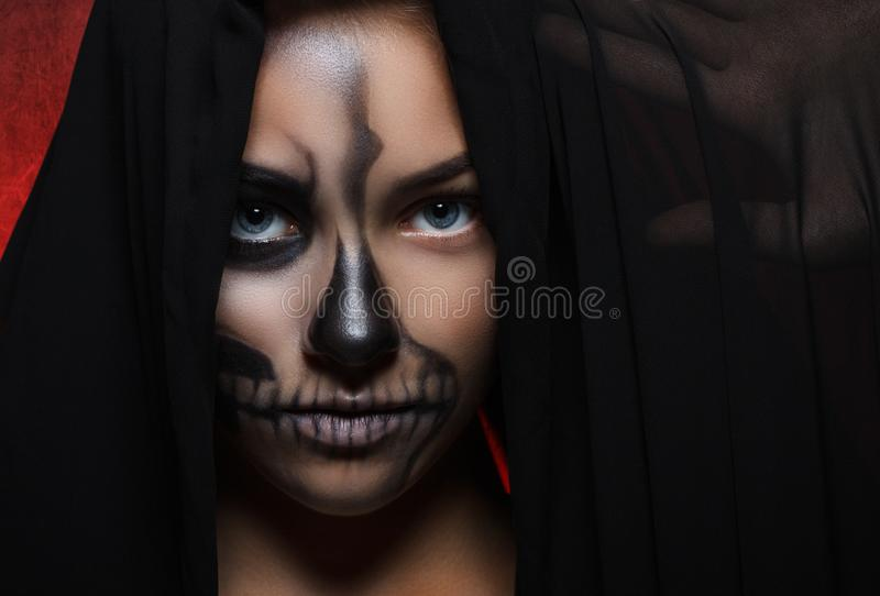 Allhelgonaaftonstående av den unga härliga flickan i en svart huv skelett- makeup royaltyfri bild