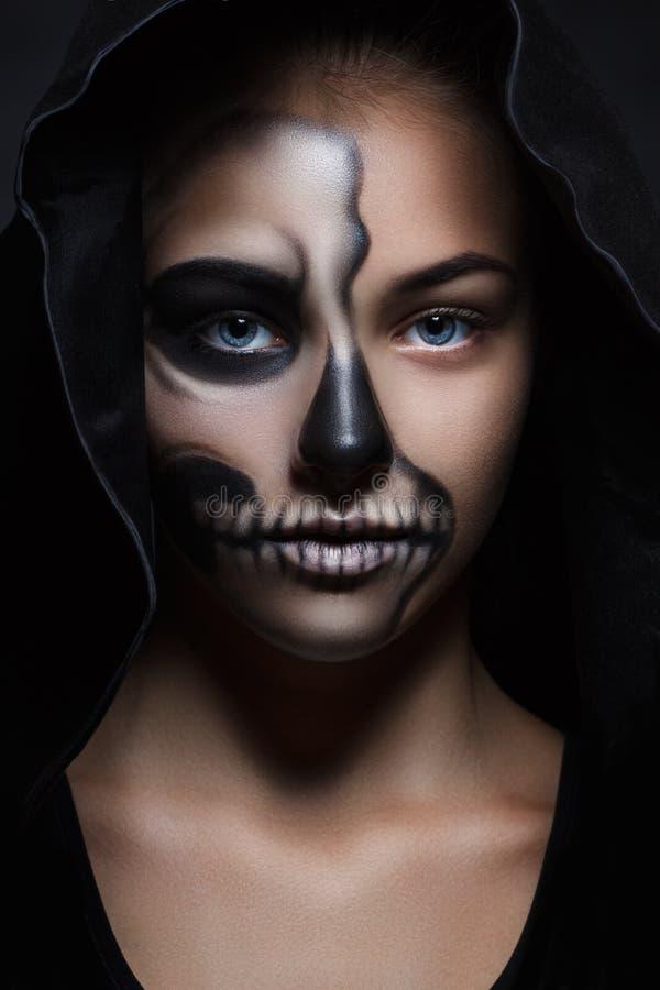 Allhelgonaaftonstående av den unga härliga flickan i en svart huv skelett- makeup arkivfoton