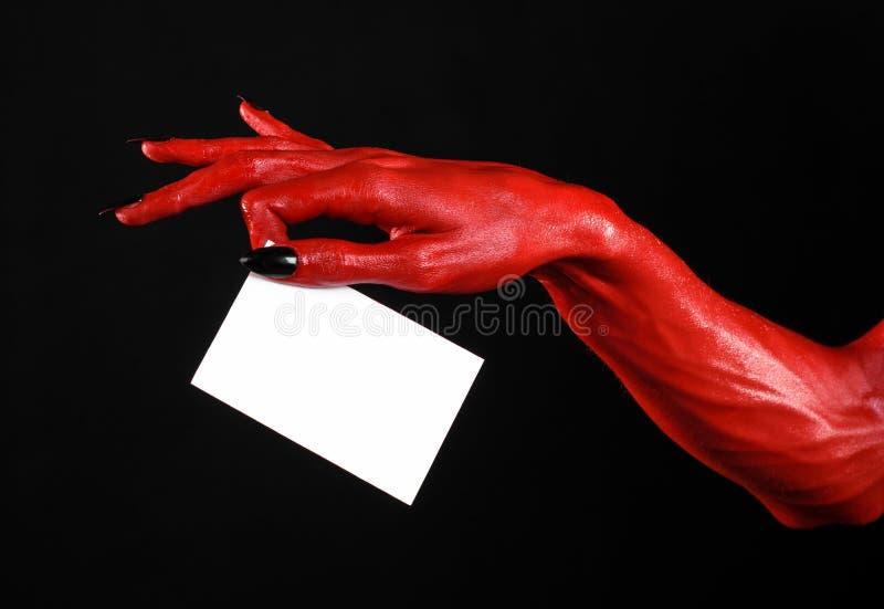 Allhelgonaaftontema: Handen för röd jäkel med svart spikar att rymma ett tomt vitt kort på en svart bakgrund royaltyfri fotografi
