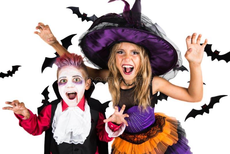 Allhelgonaaftonungar, lycklig läskig flicka och pojkeuppklädd i halloween dräkter av häxan, trollkarlen och vampyren Dracula för  royaltyfri foto