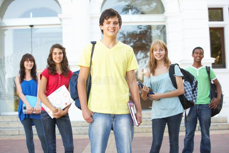 Allievi adolescenti che si levano in piedi la costruzione esterna dell'istituto universitario fotografia stock