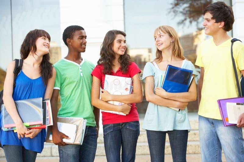 Allievi adolescenti che si levano in piedi la costruzione esterna dell'istituto universitario fotografie stock