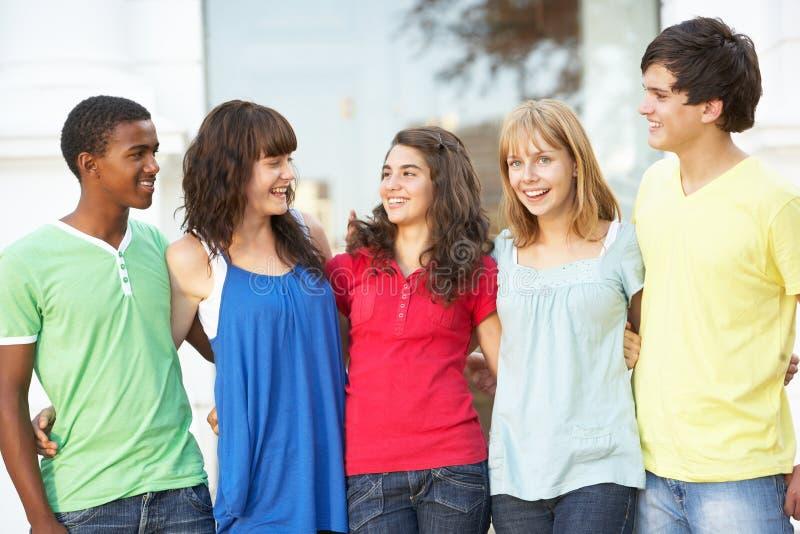 Allievi adolescenti che si levano in piedi la costruzione esterna dell'istituto universitario fotografia stock libera da diritti