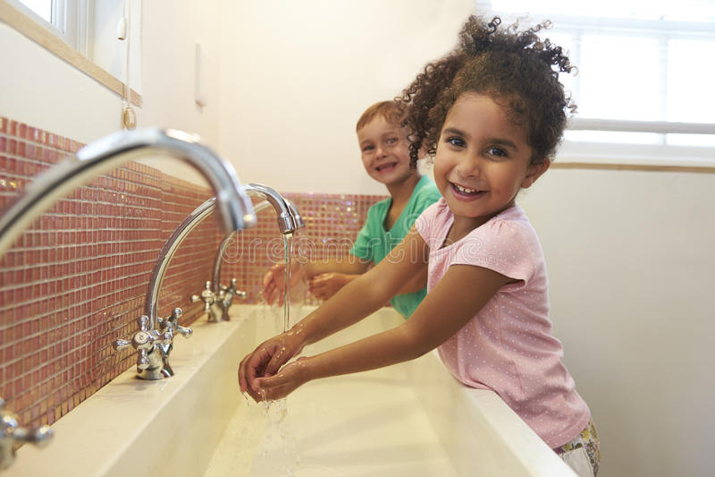 Allievi alle mani di lavaggio della scuola di Montessori in toilette immagine stock