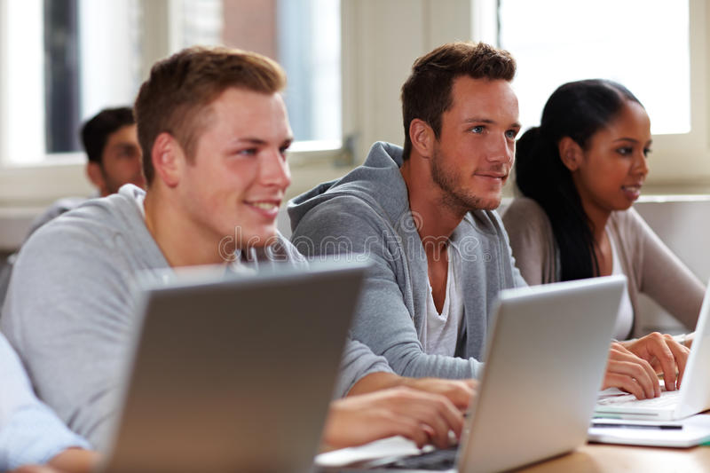Allievi che lavorano ai computer portatili fotografie stock