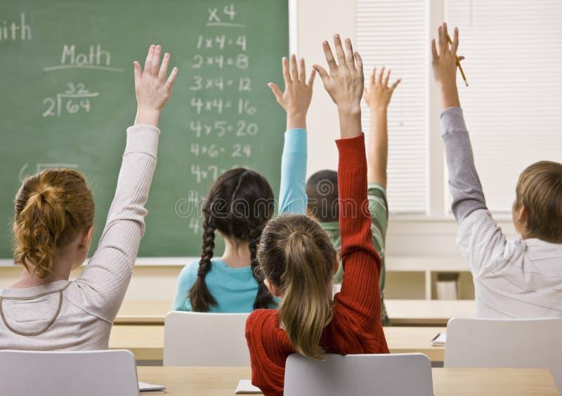 Allievi che rispondono alla domanda dell'insegnante immagine stock